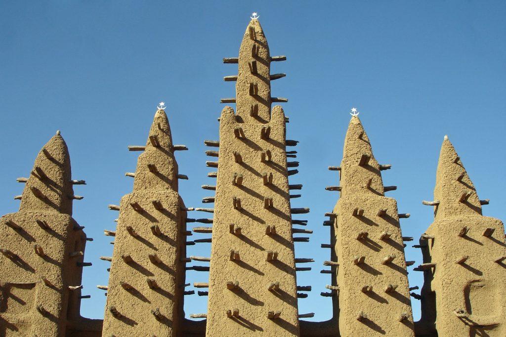 Djennen moskeija. Moskeijan seinistä ja torneista työntyy esiin palmukepukoita. Kuva: Flickr/10b travelling.