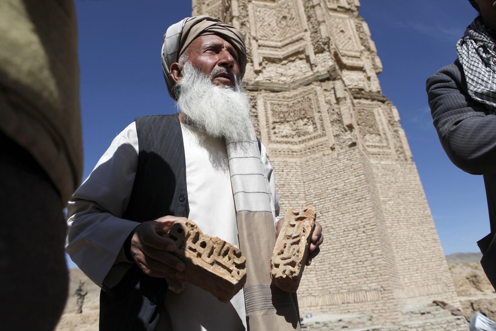 Paikallinen arkeologi Naqshbandi pitelee Ghaznin tornien edustalla käsissään tiiliskiviä, joissa on kufilaista kirjoitusta.