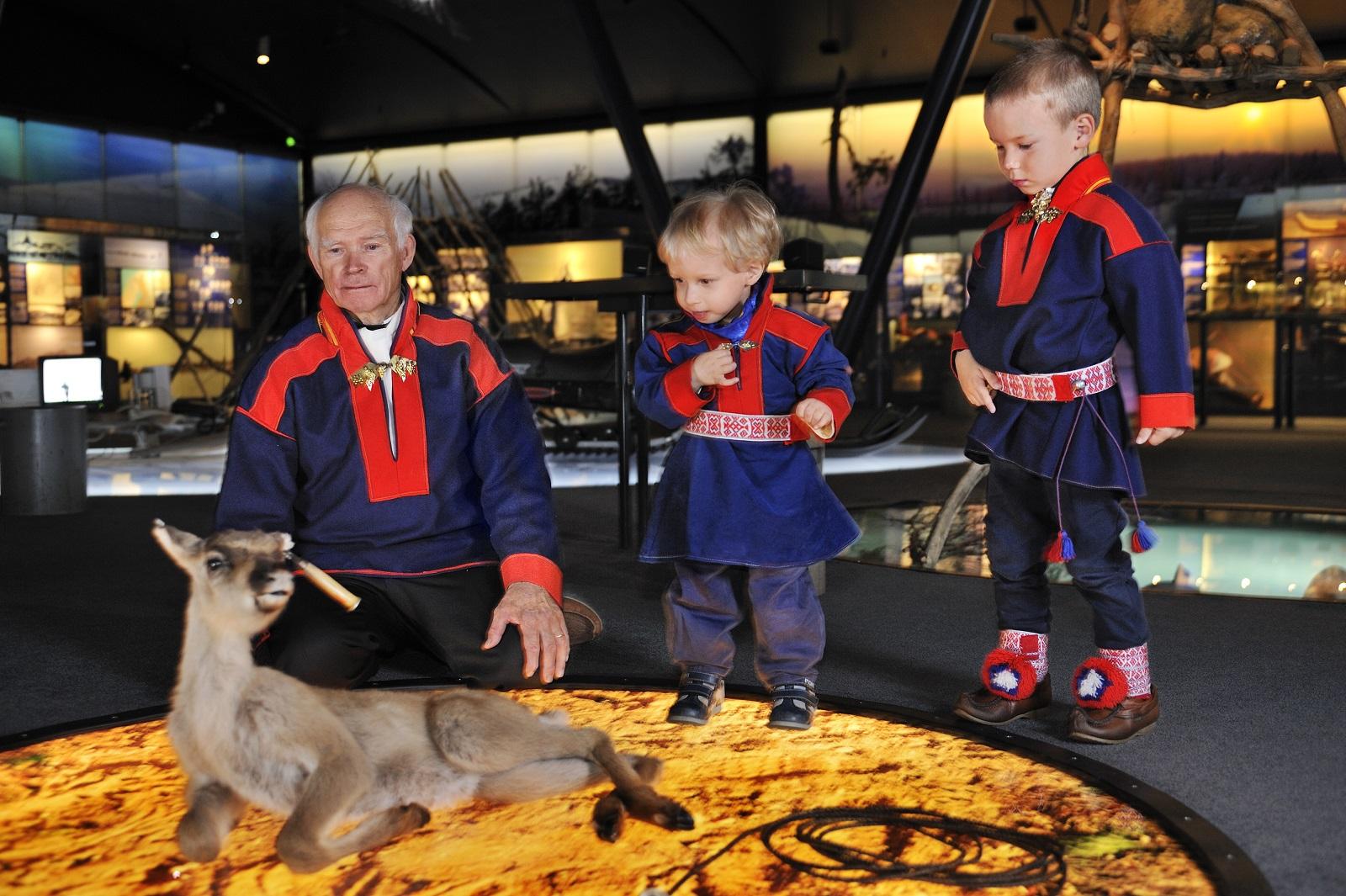 Saamelaismuseo Siida. Poromies Yrjö Mattus kertoo pojanpojalleen ja tämän kaverille entisajan poronhoidosta.