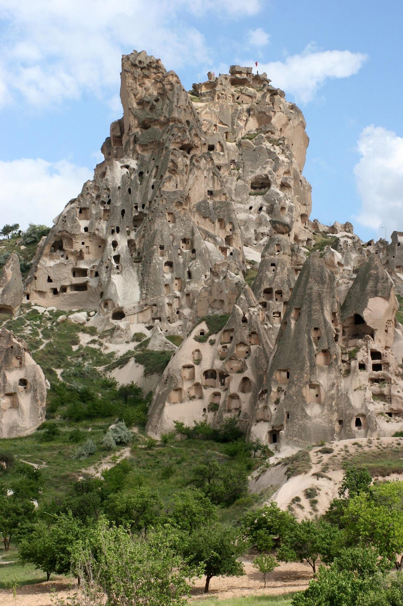 """Uchisar on Kappadokian komeimpia linnoja eli kivestä koverrettuja """"kerrostaloja"""". Sen ulkoseinät ovat romahtaneet paljastaen kammioita, jotka yhdistyvät toisiinsa portaiden, tunnelien ja käytävien avulla. Eroosion vuoksi asukkaat ovat lähteneet, mutta monet luolat ovat edelleen käytössä kyyhkyslakkoina."""