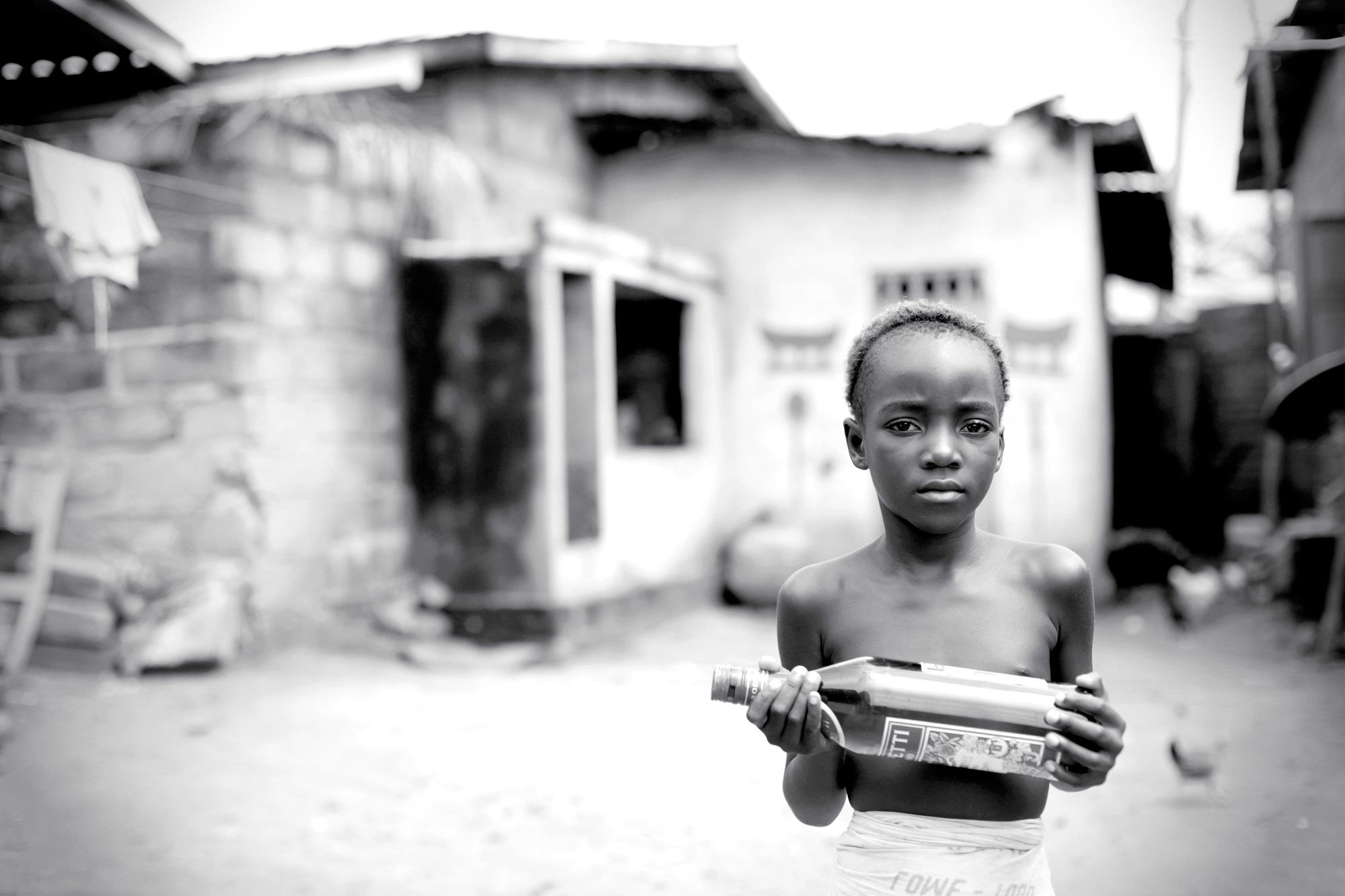 Luostarissa asuva 8-vuotias Husiga pitelee kädessään ginipulloa. Gini on jumalten suosima juoma, jota Husiga tarvitsee kasteseremoniaansa varten. Kuva: Veera Pitkänen
