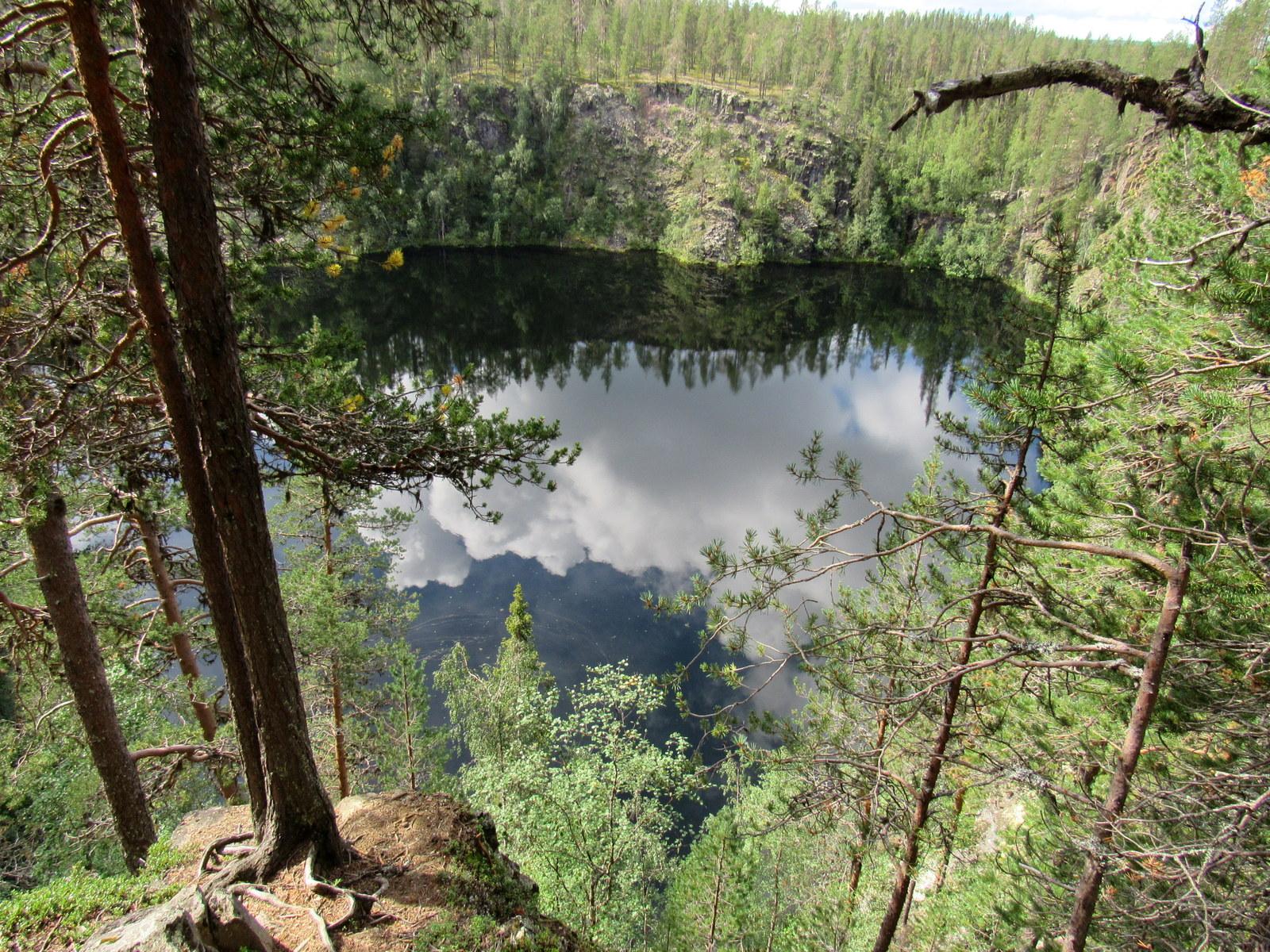 Pilvet heijastuvat Pakasaivon pintaan. Jyrkkäreunainen järvi on jopa 60 metriä syvä.