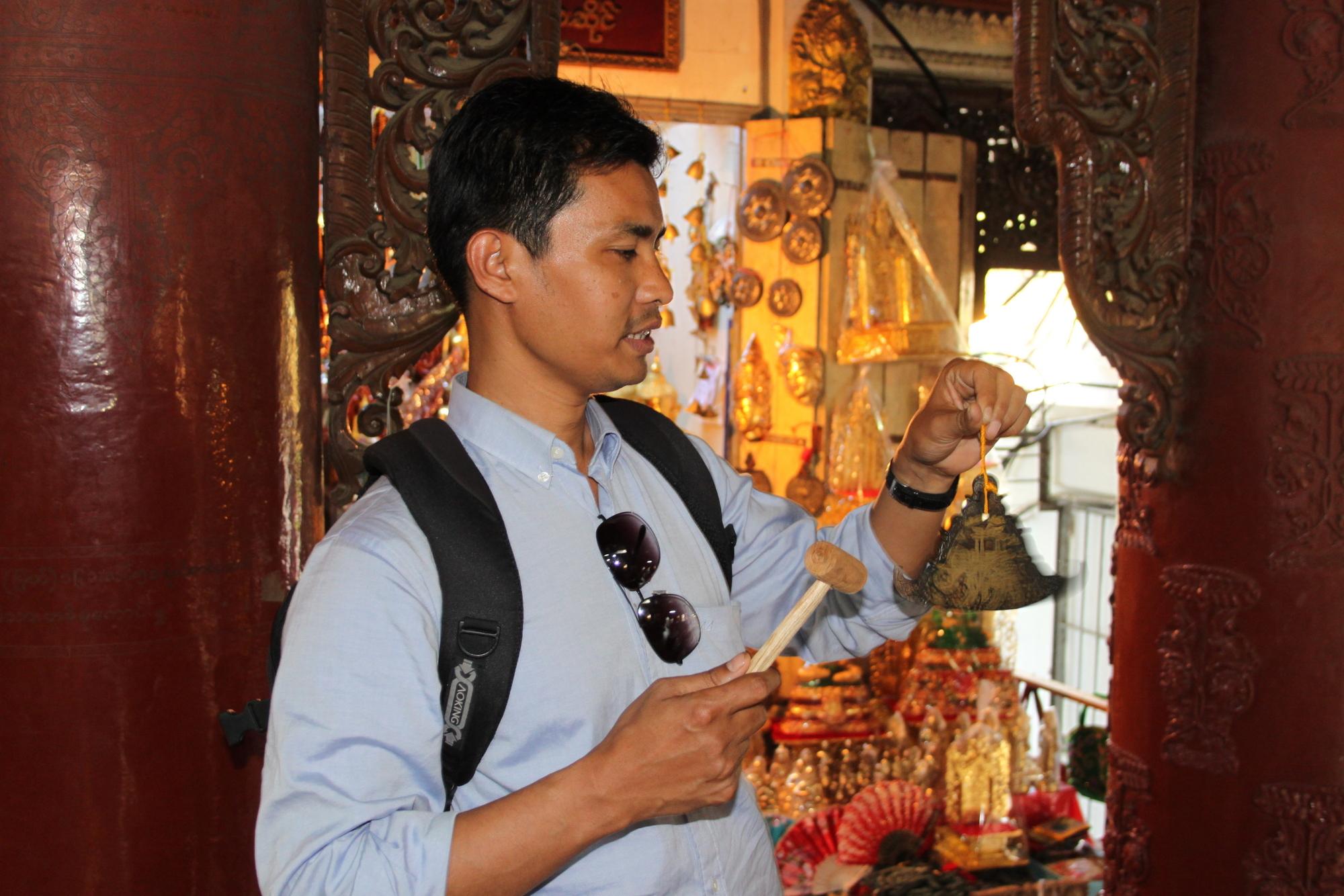 Samoe esittelee buddhalaista rukouskelloa yangonilaisella temppelillä.