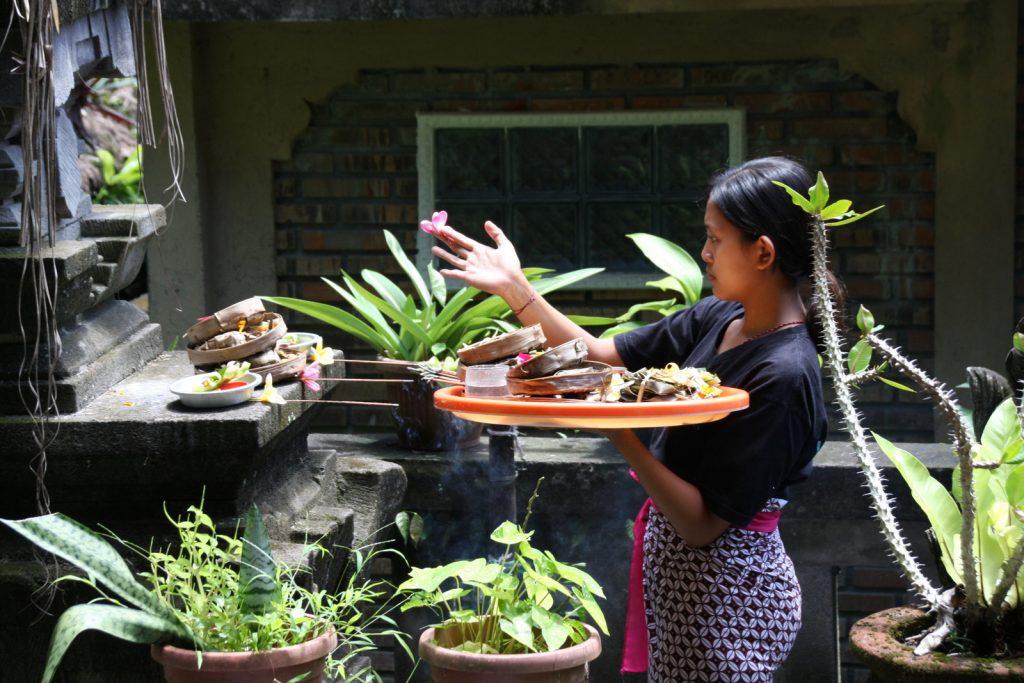 Seremoniaan liittyy kukan piteleminen. Ani´s Villas -hotelli, Ubud.